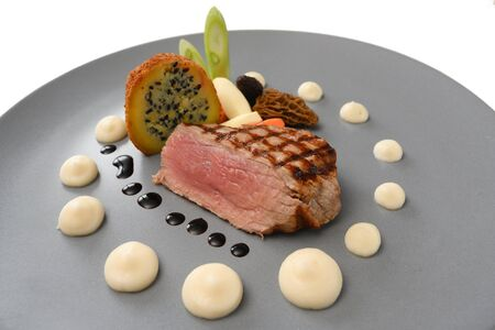 roasted veal, morels, vegetables and a fried potato stuffed with onion seeds served on a blue gray plate, selected focus, narrow depth of field