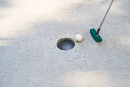 mini golf club hits the ball into the hole on a track from concrete, copy space, selected focus