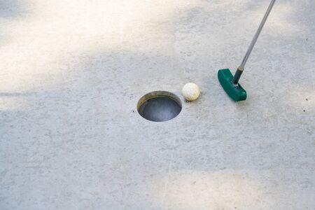 Minigolfschläger schlägt den Ball auf einer Spur aus Beton, Kopierraum, ausgewählter Fokus in das Loch