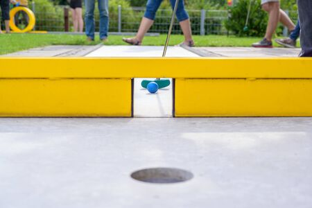 Mini golf course with a yellow obstacle gate, selected focus, narrow depth of field