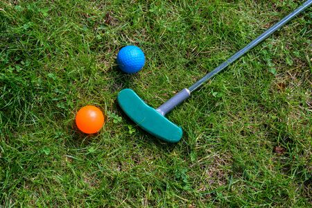 mini golf equipment, balls and a club on the grass, high angle view from above, copy space