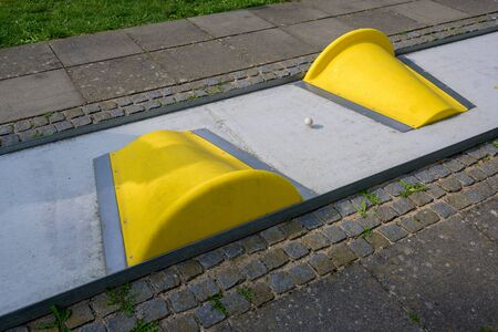 ball on the mini golf course with yellow obstacles, selected focus