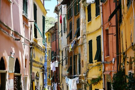 Porto Venere in Italy, typical narrow old town street with colourful houses and clotheslines, selected focus, narrow depth of field Stock Photo