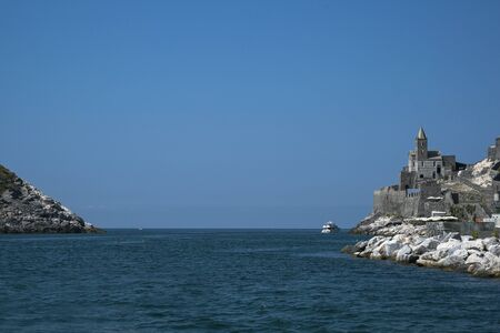 sea passage between the headland of Porto Venere with the famous Saint Peters Church and the island of Palmaria, the gate to the Cinque Terre, Liguria, Italy, blue sky with copy space