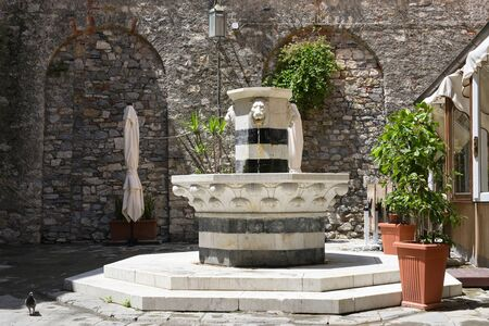 Drinking water fountain from marble with lion heads on a square in the old town of porto venere, liguria, italy