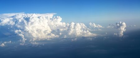 Thick clouds are accumulating at the blue sky, weather concept in panoramic format, copy space