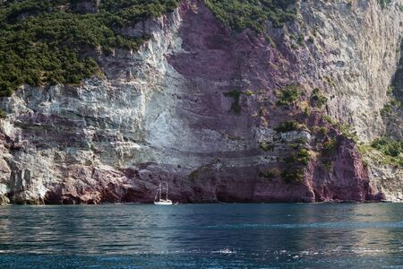 Small sailboat in a bay in front of the rocky cliffs of the Mediterranean sea 스톡 콘텐츠