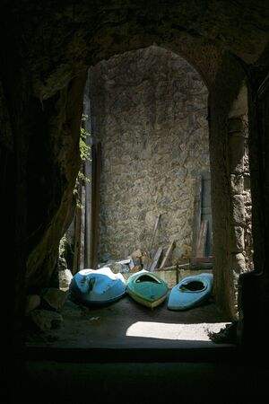 Three old rowboats in a dark alley in an historic seaport town, Liguria, Italy, copy space