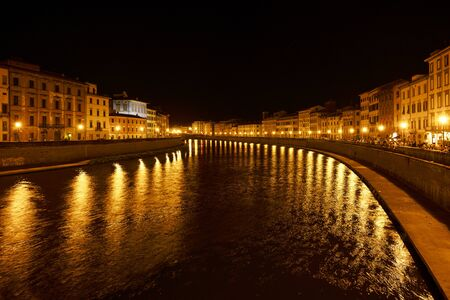 Golden lights on the Arno river shore in the old town of Pisa at night, outdoor summer nightlife with bars used by young people and tourists, copy space