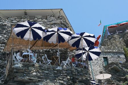 Balcony restaurant on the rocks of the steep coast on the Mediterranean sea against the blue sky in Vernazza, Cinque Terre, Italy