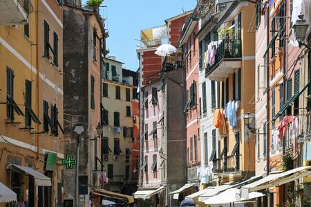 Narrow lively street with colorful houses and hanging laundry in the old town of Vernazza, Cinque Terre in Liguria, Italy Stock Photo