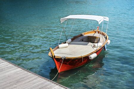 Red wooden boat with lying surface and sun canopy on the jetty in the turquoise water of the Mediterranean sea, copy space