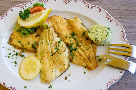 fried plaice fillet with herb butter and lemon on a plate
