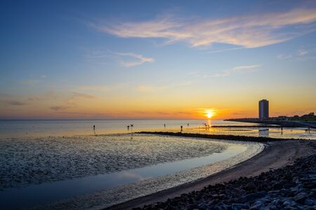 Beach and skyscraper of buesum at the north sea during ebb tide at sunset Stock Photo