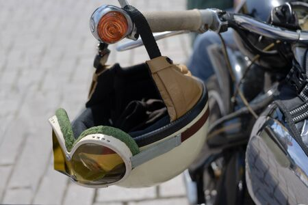 vintage crash helmet is hanging on the handlebar of a classic oldtimer motorbike, selected focus, narrow depth of field