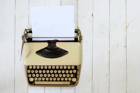 Vintage beige typewriter from the 1950s with paper on a white painted wooden background, copy space, high angle view from above, Stock Photo