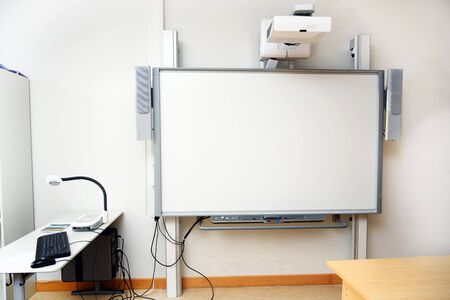 Interactive whiteboard with beamer as a modern school blackboard in the classroom, copy space