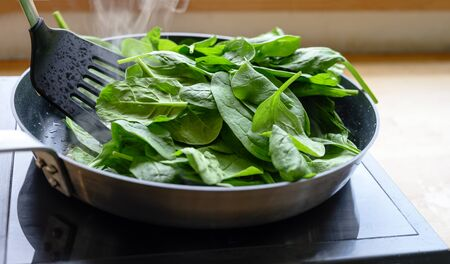 frying fresh spinach in a pan on the stove, healthy cooking at home concept, selected focus, narrow depth of field Stock Photo