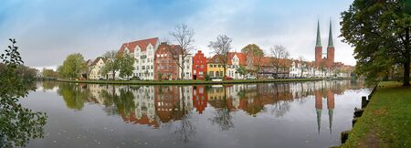 Cityscape, old town of Luebeck in Germany, wide panoramic view from the famous Malerwinkel, that means painters corner, to the historic city at the river Trave with reflections, copy space in the cloudy blue sky