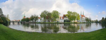 Old town of Luebeck, wide panoramic view of the historic city at the river Trave in Germany, copy space in the cloudy blue sky