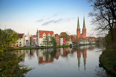 Cityscape of the historic old town of Luebeck at the Malerwinkel, that means painters corner, with the two towers of the cathedral, in German Dom, reflection in the water of the river Trave, blue sky, copy space