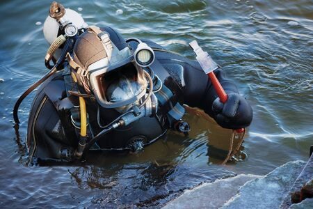industrial diver with scuba gear and hammer working in the water at the shore reinforcement, copy space