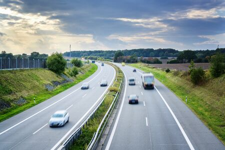 Country highway with driving cars and trucks in motion blur, concept for traffic, transport and environmental protection, copy space in the sky with clouds