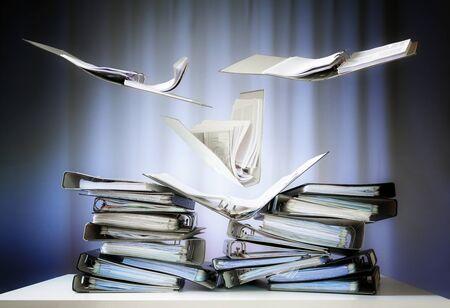 Des reliures à anneaux volantes avec des fichiers et des documents atterrissent sur des piles sur un bureau