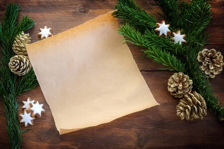Blank paper sheet between fir branches, cinnamon stars and Christmas decoration for recipe, shopping list or a wish letter to Santa Claus on a dark wooden table, copy space, top view from above