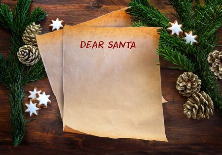 Paper sheet with text Dear Santa, between fir branches