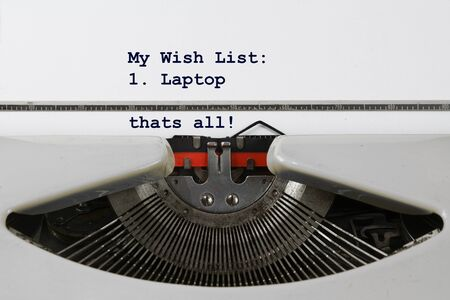 Christmas wish list written on an old typewriter with a single dot, a laptop. Concept for modernization and digitalization, selected focus, narrow depth of field 版權商用圖片