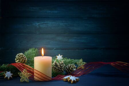 Christmas decoration with a lit white candle, fir branches, cinnamon stars and red ribbon against a dark blue wooden background, large copy space, selected focus, narrow depth of field