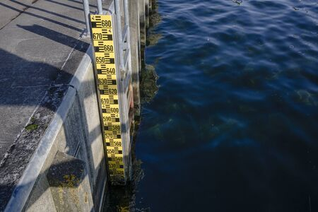 Flood measuring rod at the quay pier attached to the ladder Stockfoto