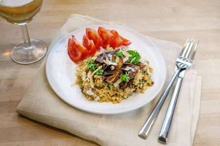Low carb diet meal, risotto made from cauliflower with dried porcini mushrooms on a plate on a wooden table