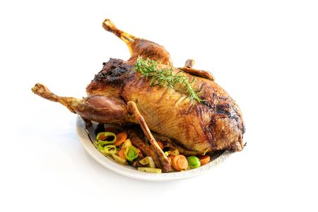 Roasted whole duck with vegetables, a festive Christmas meal isolated with small shadow on a white background, copy space, selected focus, narrow depth of field