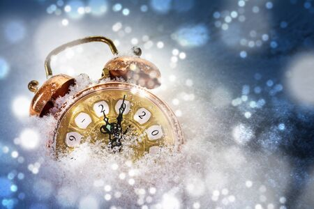 Happy New Year concept, vintage alarm clock in the snow shows 2020, greeting card with copy space