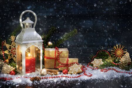 Candle light lantern and Christmas decoration in the snow against a dark blue wooden background with copy space