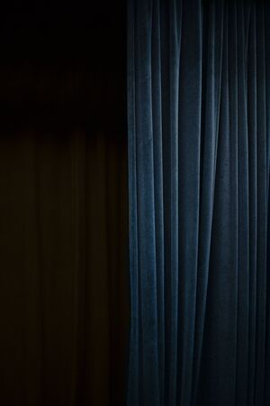 Cortina de terciopelo azul oscuro en un lado de un escenario de teatro negro, fondo de evento vertical con gran espacio de copia Foto de archivo