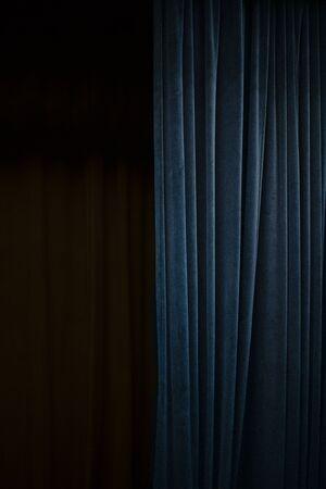 Tenda di velluto blu scuro su un lato di un palcoscenico teatrale nero, sfondo verticale dell'evento con ampio spazio di copia Archivio Fotografico