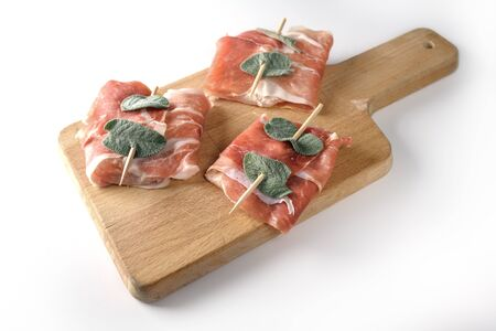 Prepared chicken saltimbocca wrapped with air-dried ham and sage leaves on a kitchen board isolated on a white background, copy space, selected focus