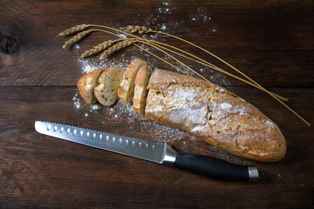 Baguette or French bread half sliced, some wheat ears and a knife on a dark rustic wood