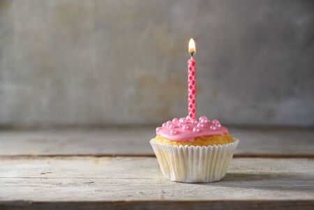 muffin or cupcake with a pink burning candle on a wooden board against a rustic background, birthday concept with copy space Stock Photo