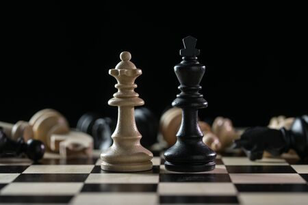 Chess pieces queen and king in front of a of fallen chessmen after a battlefield on a chessboard against a black background, concept of abuse of power, civil victims and the lack of responsibility, selected focus