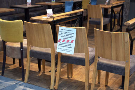 Ratzeburg, Germany, March 20, 2020: Chairs stand as a barrier in front of a café and a german massage shows that it was closed due to the spread of covid-19, coronavirus, selectded focus