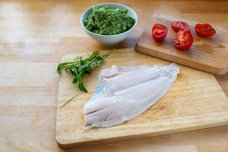 Raw plaice fillet, tomatoes and a bowl of mashed celery with arugula on a wooden kitchen board, cooking preparation to make a healthy  fish meal, copy space, selected focus, narrow depth of field