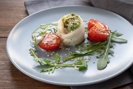 Fish fillet rolls from plaice filled with mashed celery and arugula, grilled tomatoes, rocket salad ande sesame seed on a gray plate, healthy appetizer suitable for Easter and spring time, selected focus, narrow depth of field