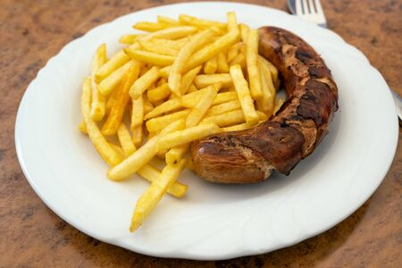 Grilled sausage, German Bratwurst, and french fries on a plate in a fast food restaurant, tasty but unhealthy eating with trans fat and saturated fatty acids, selected focus, very narrow depth of field