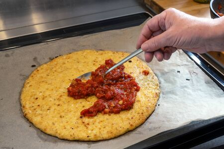 Hand is spreading tomato sauce on a pizza crust from shredded cauliflower, cooking a healthy alternative for slimming with low carb or ketogenic diet, selected focus, narrow depth of field