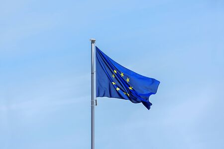 European flag with yellow stars for each member state on a blue background waving in the wind against a bright sky, large copy space on all sides, partly motion blur