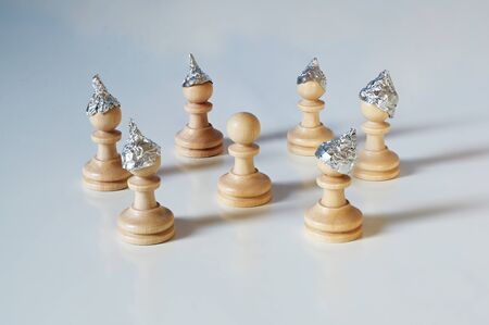 Conspiracy theory and manipulation concept in coronavirus time, group of pawn chess pieces with tinfoil helmets on their heads are surrounding a piece without a hat, gray background, copy space, selected focus